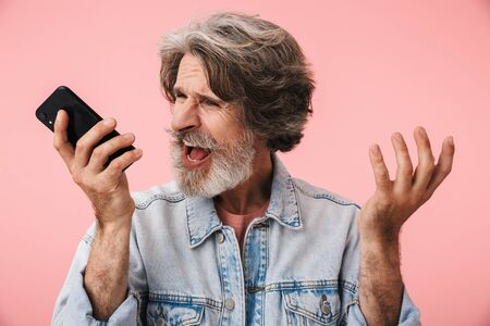 Portrait of stressed old man with gray beard expressing anxiety and screaming at cellphone isolated over pink background