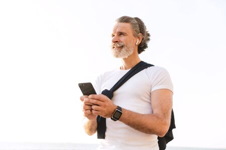 Image of pleased old man in sportswear using earpod and cellphone while working out in morning outdoors