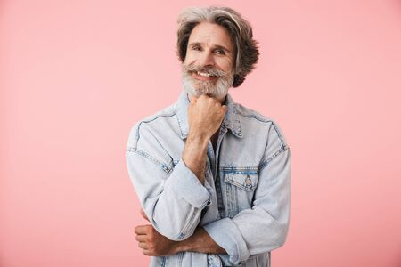 Portrait of pleased old man with gray beard smiling and looking at camera isolated over pink background