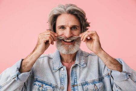 Portrait of cheerful old man with gray beard smiling at camera and touching his mustache isolated over pink background