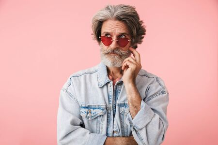 Portrait of confused old man with gray beard wearing fashion sunglasses and denim jacket looking at copyspace isolated over pink background Reklamní fotografie