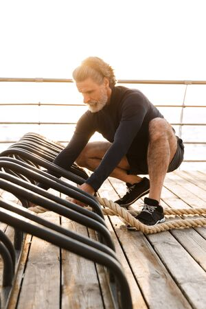 Image of bearded mature man in tracksuit doing exercise with battle ropes while working out near seaside in morning