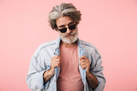 Portrait closeup of fashion old man 70s with gray beard looking at camera and touching his denim jacket isolated over pink background