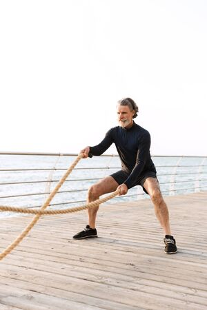 Image of sporty old man in tracksuit doing exercise with battle ropes while working out near seaside in morning