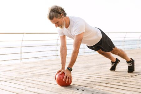 Image of sporty old man in sportswear using earpod while doing exercise with medicine ball near seaside in morning