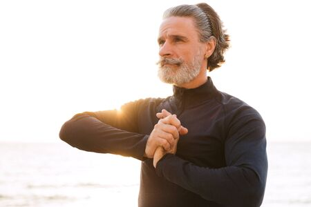 Image of sporty mature man in tracksuit doing exercise while working out near seaside in morning