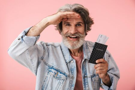 Portrait closeup of happy old man 70s with gray beard smiling while holding passport and travel ticket isolated over pink background Reklamní fotografie