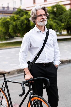 Photo of pleased mature businessman in eyeglasses walking with bicycle on city street