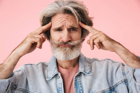 Portrait of uptight old man with gray beard looking at camera and touching his temples isolated over pink background