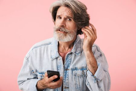 Portrait closeup of serious old man 70s with gray beard holding smartphone while listening to music with earphones isolated over pink background