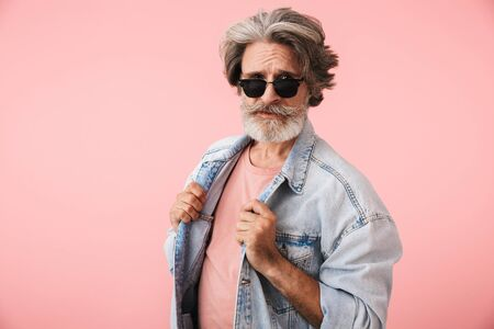 Portrait of fashion old man with gray beard wearing sunglasses and denim jacket looking at camera isolated over pink background Reklamní fotografie