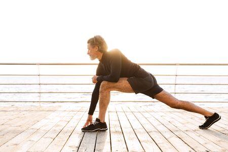 Imagen de atlético anciano en chándal haciendo ejercicio mientras se ejercita cerca de la playa en la mañana Foto de archivo