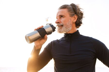 Image of athletic old man in tracksuit drinking water from bottle while working out in morning outdoors