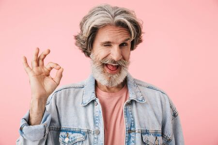 Portrait of a cheerful middle aged man wearing casual outfit standing isolated over pink background, showing ok gesture 写真素材