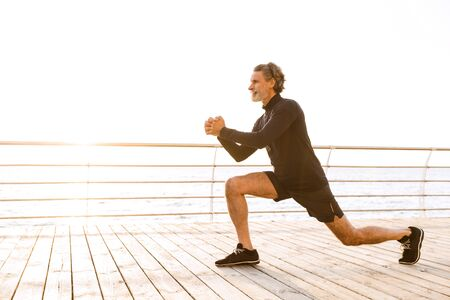 Image of strong old man in tracksuit doing exercise while working out near seaside in morning Imagens