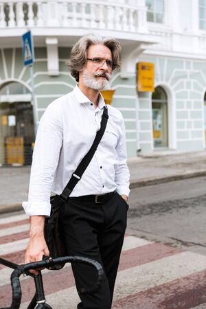 Photo of thinking mature businessman in eyeglasses walking with bicycle on city street Reklamní fotografie