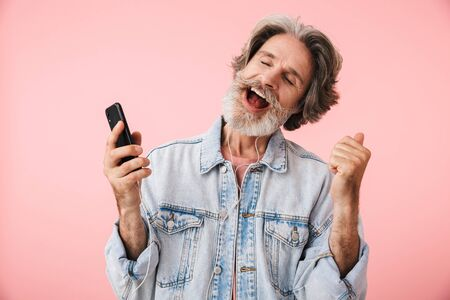 Portrait closeup of happy old man 70s with gray beard singing while listening to music with smartphone and earphones isolated over pink background