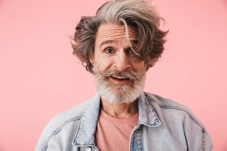 Portrait closeup of pleased mature man 70s with gray beard and messy hair smiling at camera isolated over pink background Reklamní fotografie