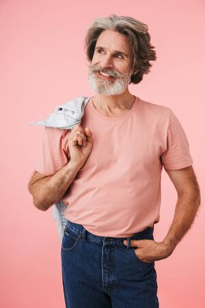 Portrait of handsome mature man 70s with gray beard smiling and holding his denim jacket over his shoulder isolated over pink background Reklamní fotografie