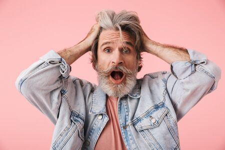 Portrait of nervous mature man with gray beard grabbing head and screaming at camera isolated over pink background