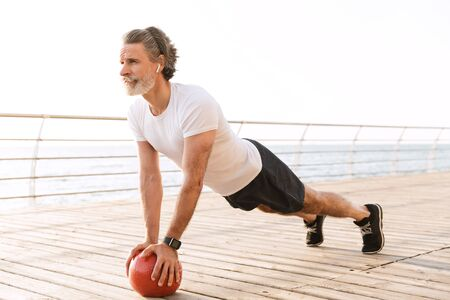 Image of bearded mature man in sportswear using earpod while doing exercise with medicine ball near seaside in morning