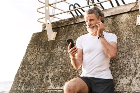 Image of focused old man in sportswear using earpod and cellphone while leaning on wall near seaside in morning