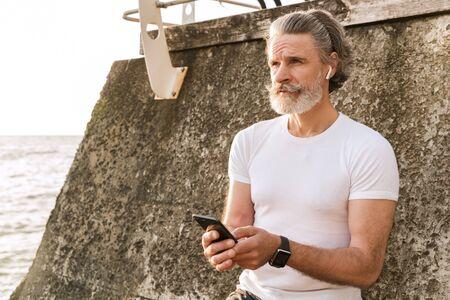 Image of caucasian elderly man in sportswear using earpod and cellphone while leaning on wall near seaside in morning