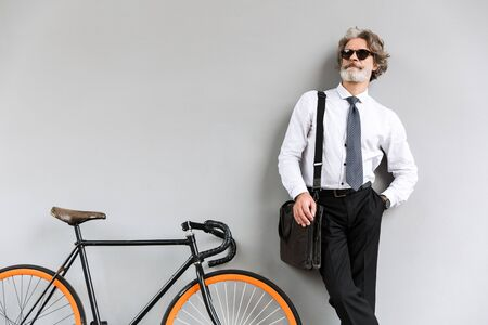 Photo of elegant old businessman in sunglasses looking upward while standing with bicycle over gray wall outdoors