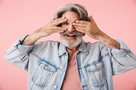 Portrait of cheerful old man with gray beard smiling and peeking from under his hands isolated over pink background