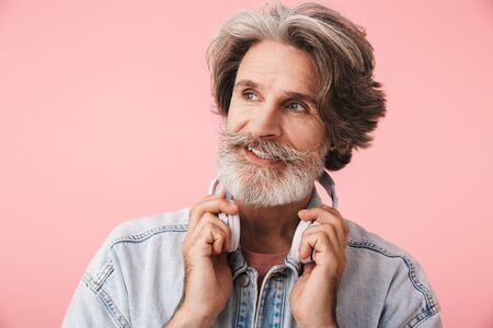 Portrait of cheerful old man with gray beard wearing denim jacket smiling and holding headphones isolated over pink background