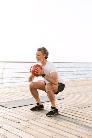 Image of focused old man in sportswear using earpod while doing exercise with medicine ball near seaside in morning Standard-Bild