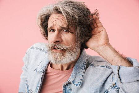 Portrait of deaf old man with gray beard trying to hear something while keeping hand at his ear isolated over pink background