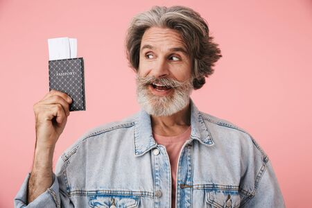 Portrait of cheerful old man with gray beard wearing denim jacket smiling while holding passport and travel ticket isolated over pink background