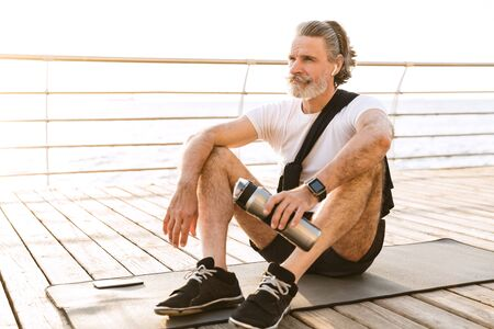 Image of masculine old man in sportswear using earpod and holding water bottle while sitting on mat at boardwalk in morning 写真素材