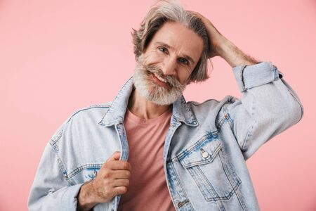 Portrait of handsome old man with gray beard smiling and looking at camera isolated over pink background 写真素材