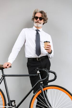 Photo of satisfied old businessman in sunglasses drinking coffee takeaway while standing with bicycle over gray wall outdoors Reklamní fotografie