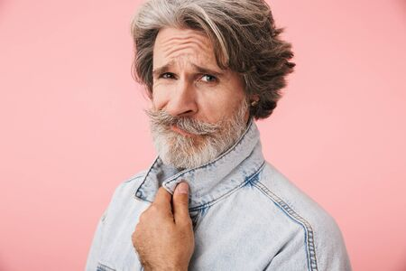 Portrait of mustached old man with gray beard wearing denim jacket looking at camera isolated over pink background