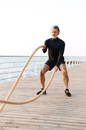 Image of concentrated elderly man in tracksuit doing exercise with battle ropes while working out near seaside in morning 免版税图像