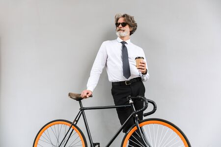 Photo of bearded mature businessman in sunglasses drinking coffee takeaway while standing with bicycle over gray wall outdoors