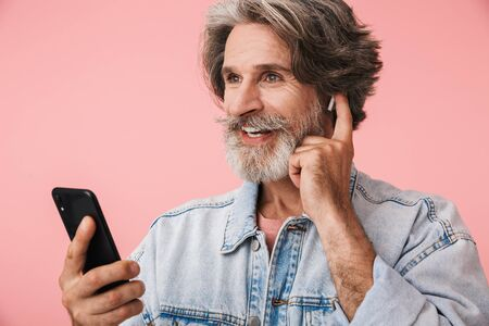 Portrait of joyful old man with gray beard wearing denim jacket listening to music with cellphone and earpods isolated over pink background