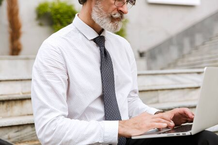 Cropped photo of bearded gray-haired businessman in eyeglasses typing on laptop while sitting outdoors