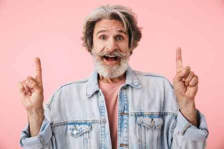 Portrait of satisfied old man with gray beard laughing and pointing fingers at copyspace isolated over pink background