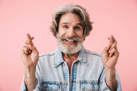 Portrait of happy old man with gray beard smiling and begging with fingers crossed isolated over pink background