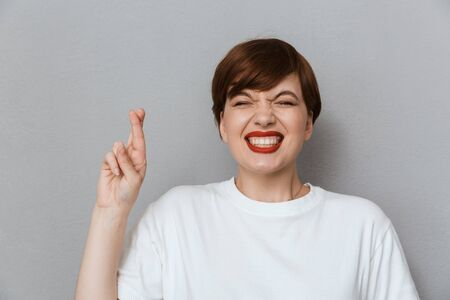 Image of happy brunette woman wearing casual t-shirt keeping fingers crossed isolated over gray background