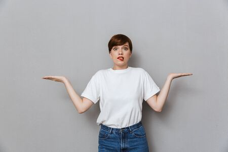 Image of puzzled young woman shrugging and throwing up hands isolated over gray background