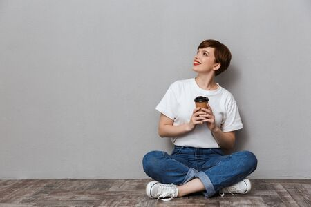 Image of gorgeous woman looking aside while sitting on floor with takeaway coffee cup isolated over gray background