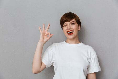 Image of young brunette woman wearing casual t-shirt showing ok sign with fingers isolated over gray background