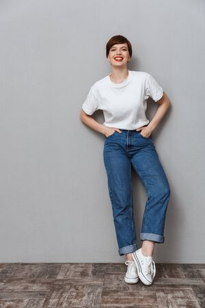 Full length image of pretty brunette woman wearing jeans smiling at camera isolated over gray background