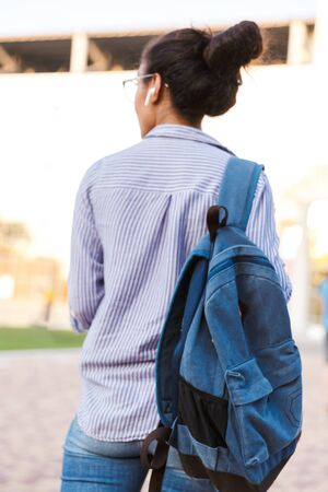 Back view of an attractive young african woman student carrying backpack walking outdoors, listening to music with wireless earphones