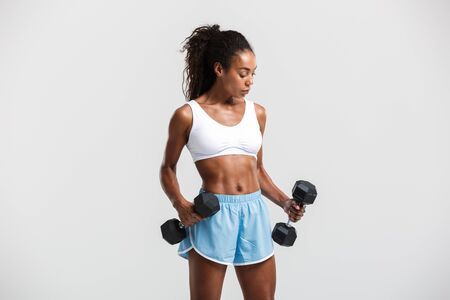 Portrait of an attractive healthy fit confident african sportswoman exercising with dumbbells isolated over white background